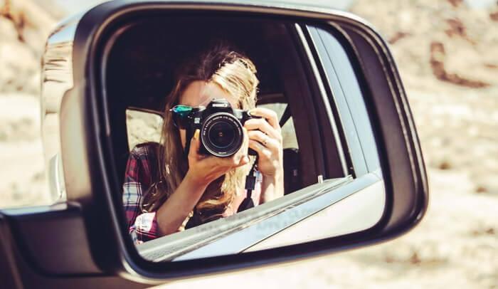 Dies ist ein Foto von einer Frau, die sich im Autospiegel fotografiert.